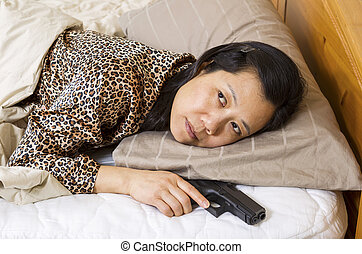 Mature woman awake in bed with personal weapon in hand