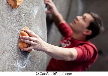 rock climbing indoors - young caucasian man rock climbing...