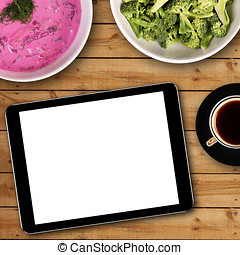 digital tablet with white blank screen on dinner table