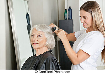 Hairstylist Straightening Woman's Hair At Salon - Senior...