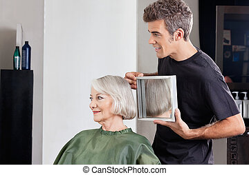 Hairstylist Showing Finished Haircut To Customer At Parlor -...