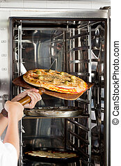 Chef's Hands Placing Pizza In Oven