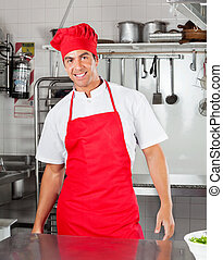 Chef Standing In Commercial Kitchen - Portrait of happy chef...