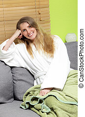 Mid aged woman sitting on the couch with toothy smile