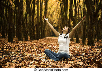 Happy woman seated on the ground with arms open