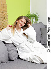 Beautiful mid aged woman in bathrobe sitting on a grey couch