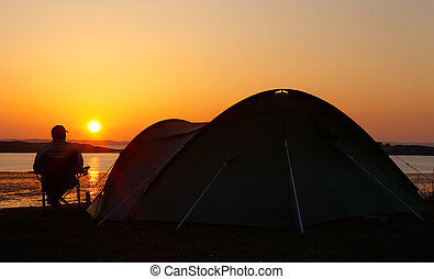 sunsets behind camper and tent - sun sets on the horizon...