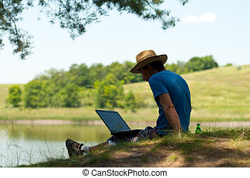 Man with notebook on river bank on summer day - freelancer
