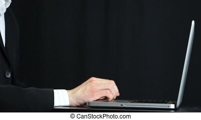 Working with Laptop Low Key - A businessman typing on a...