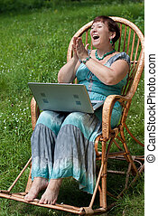 Happy mature woman with laptop in rocking chair handclapping...
