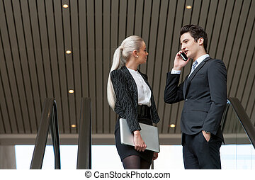 Business couple talking on phone in mall.