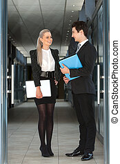 Portrait of business couple with file and laptop.