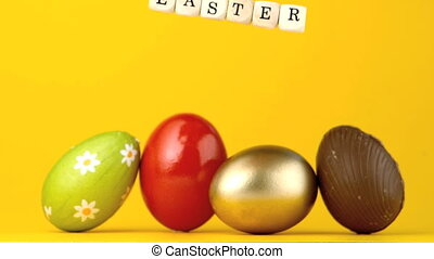 Dice spelling out easter falling in front of four eggs in...