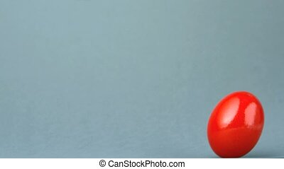 Red egg revolving against grey background in slow motion