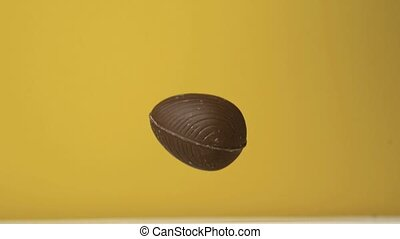 Chocolate easter egg falling against yellow background in...