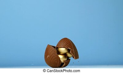 Chocolate easter egg falling against blue background in slow...