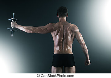 Back of young male bodybuilder doing weight exercise with...