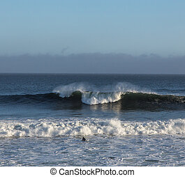 A Solitary Surfer Appraoches the Waves near Natural Bridges...