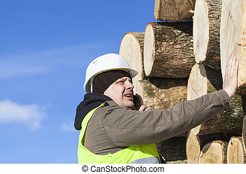Forester talking on the cell phone near at the log pile