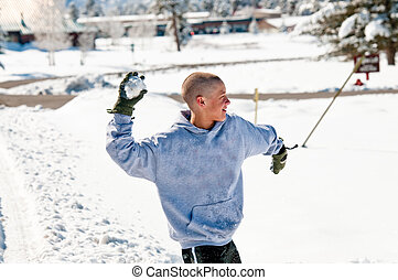 Bald boy throwing snowball - Happy bald boy wearing a hood...