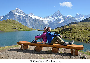 Travelers on a bench enjoying Alpine panorama. Jungfrau...