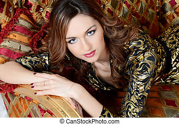 The elegant woman on a magnificent sofa close up