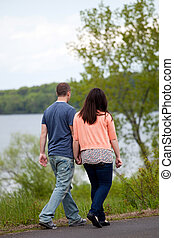 Couple Taking a Walk - Young happy couple enjoying each...