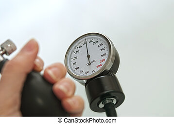 High Blood Pressure - Blood pressure gauge and a human hand...