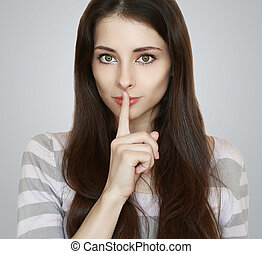 Beautiful woman with secret holding finger over lips -...