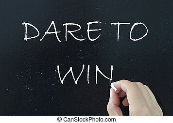 Dare to win written with chalk on a blackboard