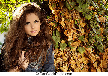 Young beautiful woman outdoors portrait. Soft sunny colors.