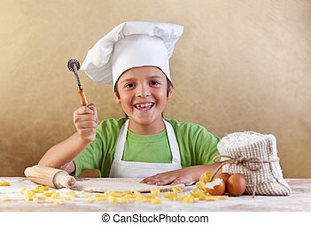 Happy kid with chef hat making pasta or cookie with the...
