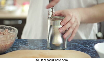 man opening can in the kitchen - man opening tin in the...