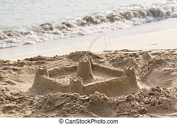 Childs sand castle on beach by ocean - Sandcastle built in...