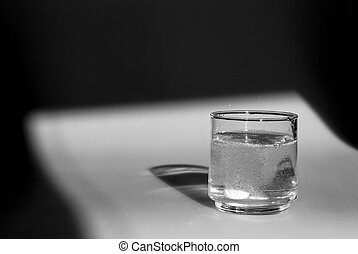 alka seltzer fizzing in the bottom of a glass - glass of...