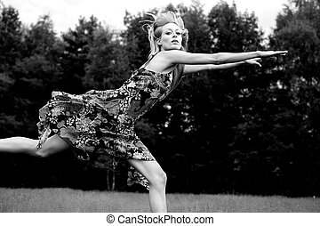 High Fashion Nature - Young blond woman wearing a dress in...