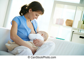 Feeding baby - Portrait of happy woman holding her small son...