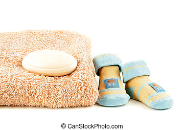 baby bathtime - baby sock and soap beside  a towel