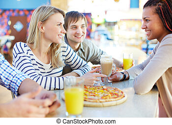 Talking in bar - Image of teenage friends interacting in...