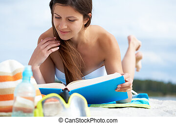 Reading on the beach - Image of pretty female lying on the...