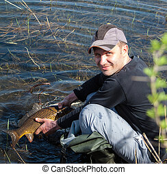 Happy lucky fisherman holding a big carp on the river Early...