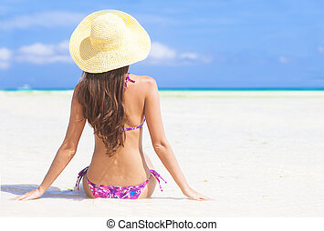 back view of young woman in straw hat with closed eyes on...