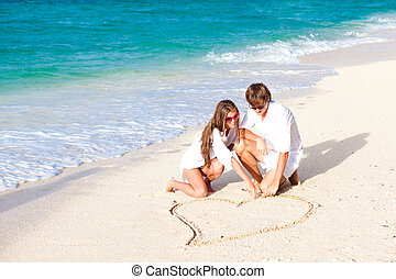 young happy couple drawing heart on tropical beach. honeymoon