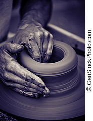Old man hands working on pottery wheel