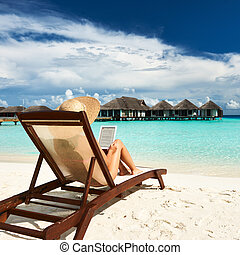 Young woman with tablet pc at the beach - Young woman in hat...