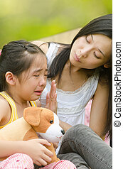 asian chinese girl crying while being comfort by her mother,...