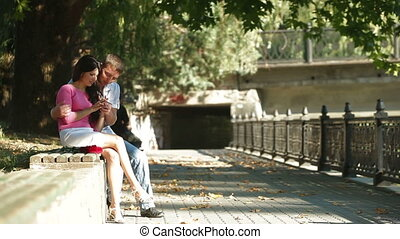 Young couple date in the city - A young couple sitting in a...