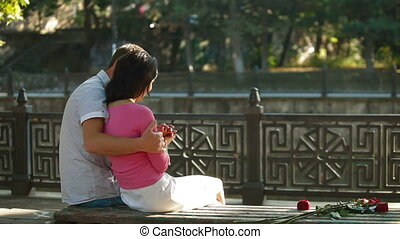 Urban loving couple - Young couple sitting embraced on a...