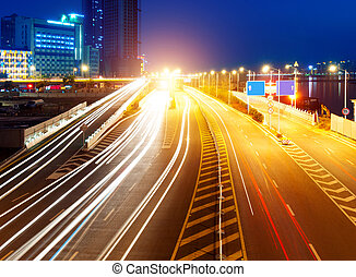 highway light trails - Highway light trails, modern city at...
