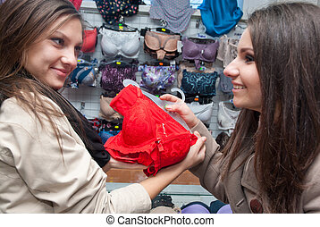 Two women buying lingerie - Young woman buying red lingerie...